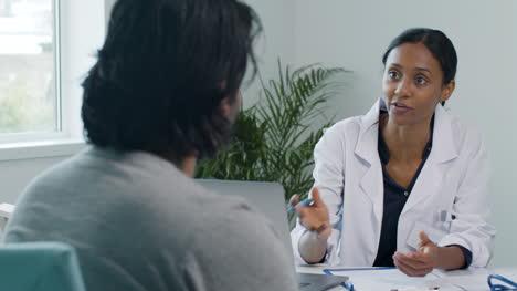 Joven-Médico-Usando-El-Portapapeles-Y-Hablando-Con-El-Paciente