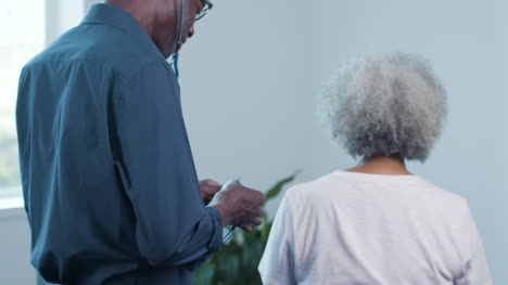 Middle-Aged-Male-Doctor-Uses-Stethoscope-On-Patient-s-Back