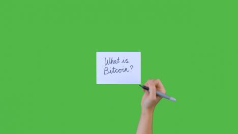 Mujer-Escribiendo-Qué-Es-Bitcoin-En-Cursiva-Sobre-Papel-Con-Pantalla-Verde