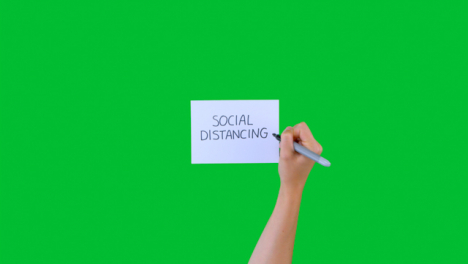Woman-Writing-Social-Distancing-on-Paper-with-Green-Screen