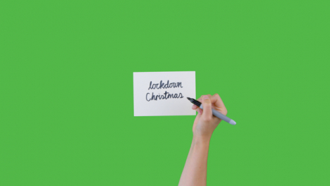 Woman-Writing-Lockdown-Christmas-on-Paper-with-Green-Screen