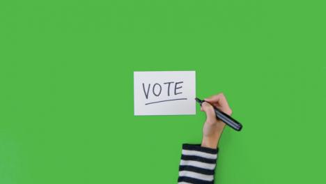 Mujer-Escribiendo-Voto-En-Papel-Con-Pantalla-Verde
