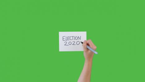 Mujer-Escribiendo-Elecciones-2020-En-Papel-Con-Pantalla-Verde