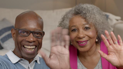 Older-Couple-Waving-Hello-and-Listening-During-Video-Phone-Call