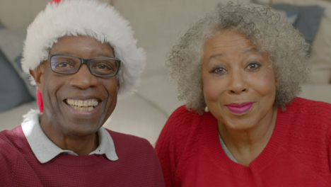 Older-Couple-Waving-Hello-and-Listening-During-Christmas-Video-Call