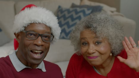 Older-Couple-Waving-Hello-and-Listening-Intently-During-Christmas-Video-Call