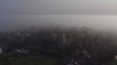 Drone-Shot-Orbiting-Islip-Church-In-Mist-01
