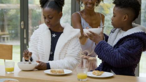 Madre-Le-Da-A-Sus-Hijos-Tazones-De-Cereal-Durante-El-Desayuno