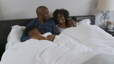 Family-Snuggling-In-Parents-Bed-Together-