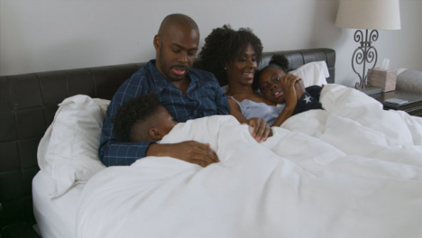 Children-Snuggling-with-Their-Parents-In-Bed