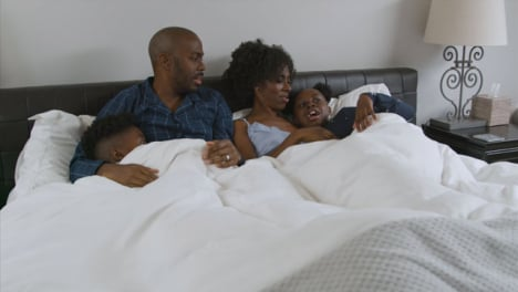 Young-Children-Snuggling-In-Their-Parents-Bed