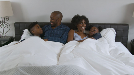 Young-Children-Snuggle-In-Their-Parents-Bed