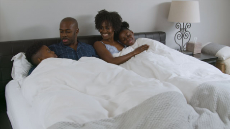 Middle-Aged-Couples-Children-Snuggle-with-Them-In-Their-Bed