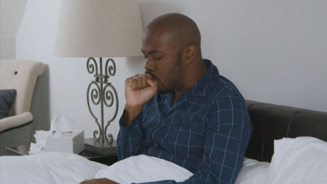 Middle-Aged-Man-Coughing-and-Holding-Head-In-Bed
