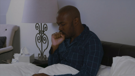 Middle-Aged-Man-Feeling-Ill-In-Bed-Uses-a-Tissue-and-Blows-His-Nose