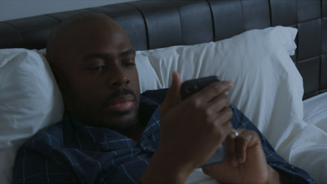 Middle-Aged-Man-Laying-In-Bed-Looking-at-His-Smartphone-
