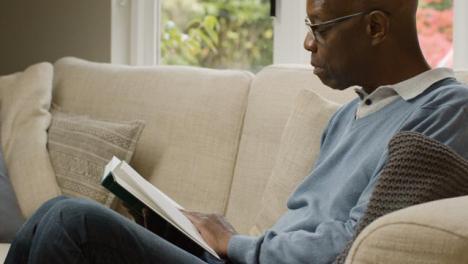 Mann-Mittleren-Alters-Sitzt-In-Seinem-Wohnzimmer-Und-Liest-Ein-Buch