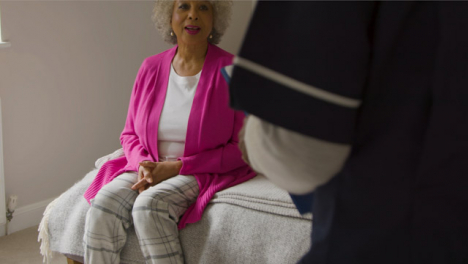 Middle-Aged-Nurse-Conducts-Home-Visit-with-Elderly-Woman