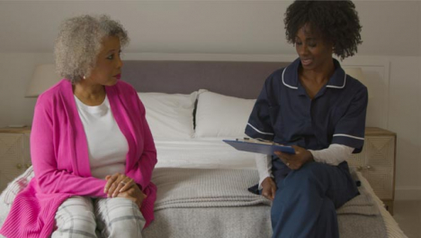 Middle-Aged-Nurse-Conducting-Home-Visit-with-Elderly-Woman