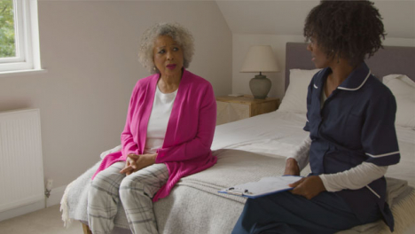 Middle-Aged-Nurse-Conducting-Home-Visit-with-Senior-Woman