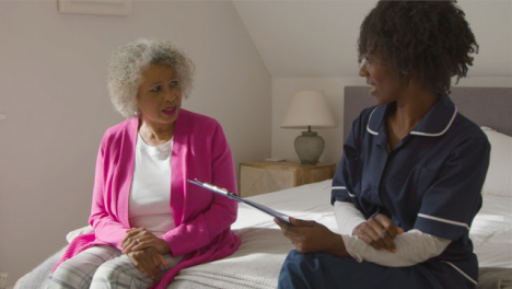 Middle-Aged-Nurse-Conducting-a-Home-Visit-with-Senior-Woman