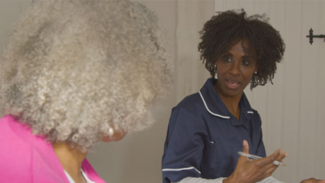 Middle-Aged-Nurse-Conducting-a-Home-Visit-In-Senior-Womans-Bedroom
