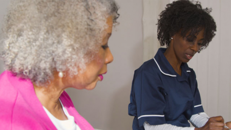Middle-Aged-Nurse-Conducting-Home-Visit-In-Senior-Womans-Home