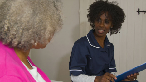 Middle-Aged-Nurse-Conducting-a-Home-Visit-In-Senior-Womans-Home