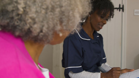 Middle-Aged-Nurse-Conducting-a-House-Visit-In-Senior-Womans-Home