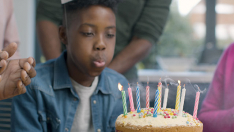 Young-Boy-Blows-Out-Candle-On-Cake-After-Family-Sings-Happy-Birthday