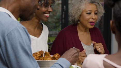 Family-Plating-Up-Food-On-Their-Plates-During-Evening-Meal-