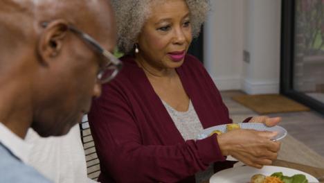Senior-Member-of-Family-Plating-Up-Potatoes-During-Dinner