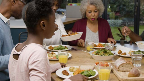 Family-Plating-Up-and-Eating-Evening-Meal-Together
