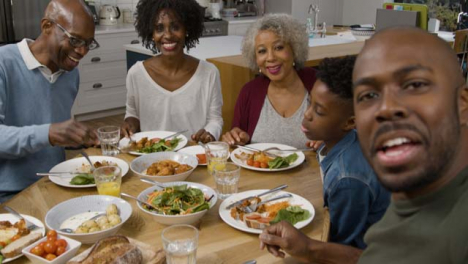 Familie-Die-Während-Des-Videoanrufs-Beim-Abendessen-Direkt-In-Die-Kamera-Spricht