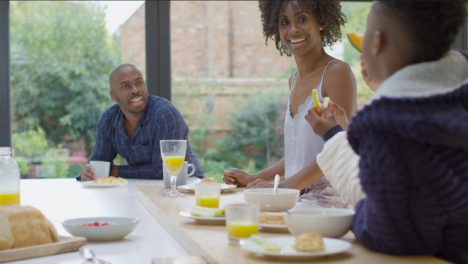 Family-Talking-and-Laughing-Together-Over-Breakfast-at-Kitchen-Island