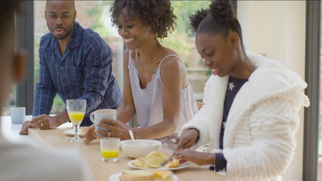 Family-Talking-and-Laughing-With-One-Another-Over-Breakfast-at-Kitchen-Island