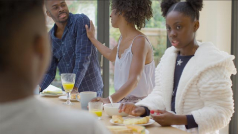 Family-Talking-and-Laughing-With-Each-Another-Over-Breakfast-at-Kitchen-Island