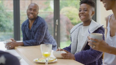 Young-Girl-Making-Her-Brother-and-Parents-Laugh-During-Breakfast