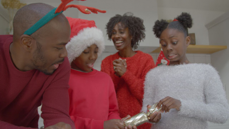 Young-Children-Try-Pulling-Christmas-Cracker-During-Family-Video-Call-