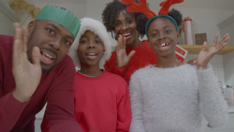 Joyful-Family-Waving-Hello-and-Talking-into-Webcam-During-Christmas-Video-Call