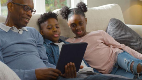Grandfather-Reading-Story-to-His-Grandchildren-from-Electronic-Tablet