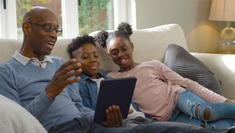 Grandfather-Reading-a-Story-to-His-Grandchildren-from-Electronic-Tablet