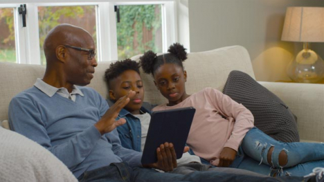 Grandfather-Reading-a-Story-to-Grandchildren-from-Electronic-Tablet