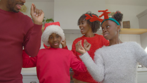 Joyful-Family-Dancing-Playfully-Together-During-Christmas-Video-Call-