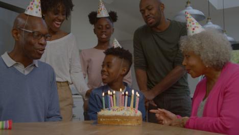 Familia-Cantando-Feliz-Cumpleaños-Para-Un-Pariente-Joven-Antes-De-Que-él-Apague-Las-Velas