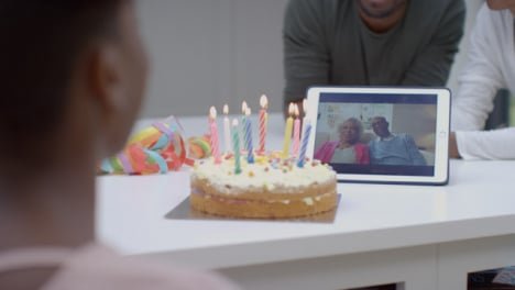 Family-Having-Video-Call-with-Grandparents-Singing-Happy-Birthday-for-Young-Daughter