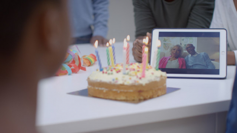 Family-Having-Video-Call-with-Grandparents-Singing-Happy-Birthday-for-Young-Girl
