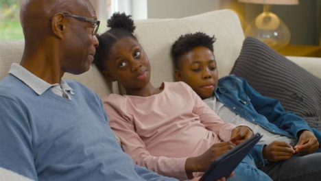 Grandfather-Reading-a-Story-On-an-Electronic-Tablet-to-Grandchildren