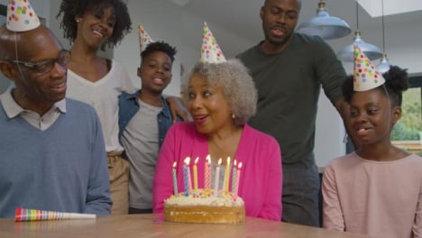 Family-Singing-Happy-Birthday-for-Elderly-Relative-Before-She-Blows-Out-Cake-Candles