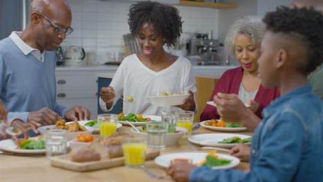 Family-Start-Plating-Up-Dinner-Together-at-Dining-Table-